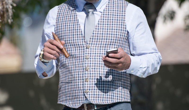 businessman-wearing-waistcoat-using-mobile-phone-and-holding-cigar